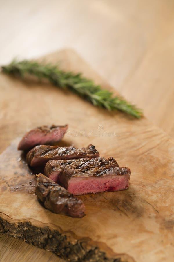Sliced medium filet mignon on wood board. M shallow focus royalty free stock photo