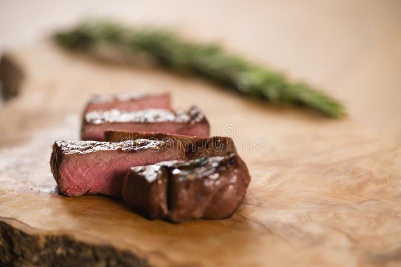 Sliced medium filet mignon on wood board. M shallow focus royalty free stock images