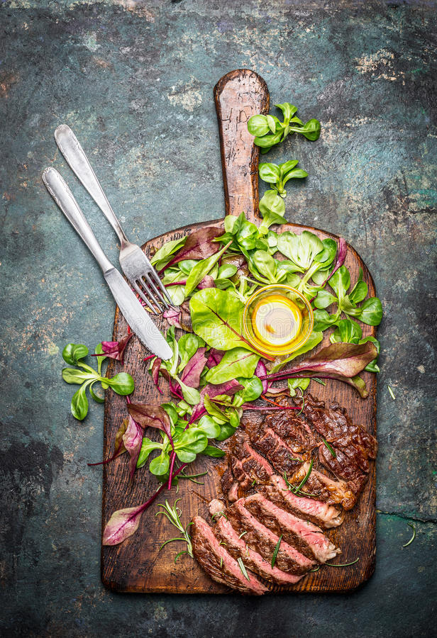 Sliced medium rare grilled beef barbecue steak served with fresh green salad and cutlery on rustic cutting board , top view. royalty free stock image