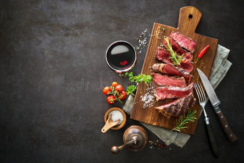 Sliced medium rare grilled beef ribeye steak. On cutting board on dark background royalty free stock image
