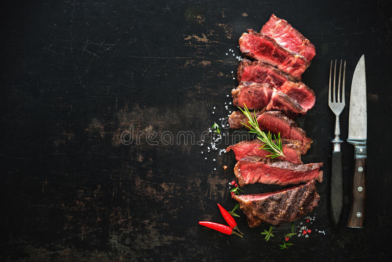 Sliced medium rare grilled beef ribeye steak. On dark background royalty free stock photography