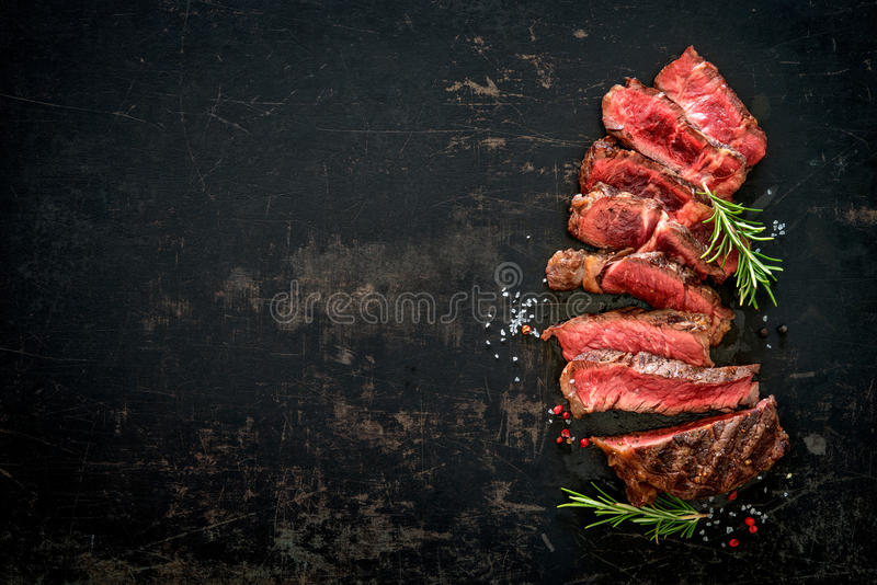Sliced medium rare grilled beef ribeye steak. On dark background royalty free stock photo