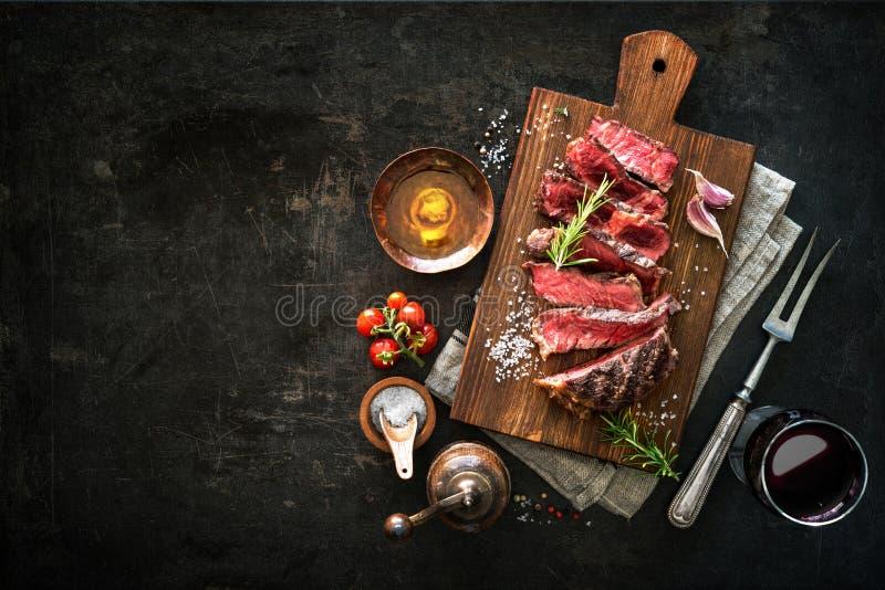 Sliced medium rare grilled beef ribeye steak. On cutting board on dark background royalty free stock photos