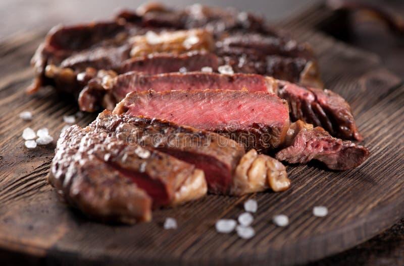 Sliced medium rare grilled beef steak ribeye close-up royalty free stock images