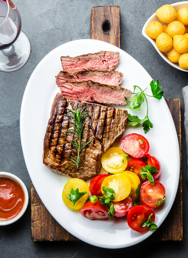 Sliced medium rare grilled beef steak served on white plate with tomato salad and potatoes balls. Barbecue, bbq meat stock photo
