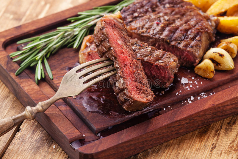 Sliced medium rare grilled steak Ribeye. Sliced medium rare grilled Beef steak Ribeye with roasted potato wedges on cutting board on wooden background royalty free stock image