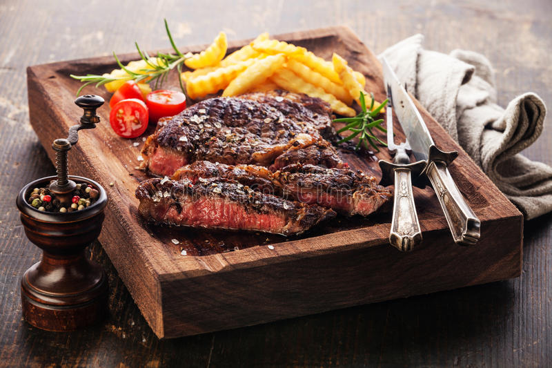 Sliced medium rare grilled Steak Ribeye with french fries. On serving board block on wooden background stock photos