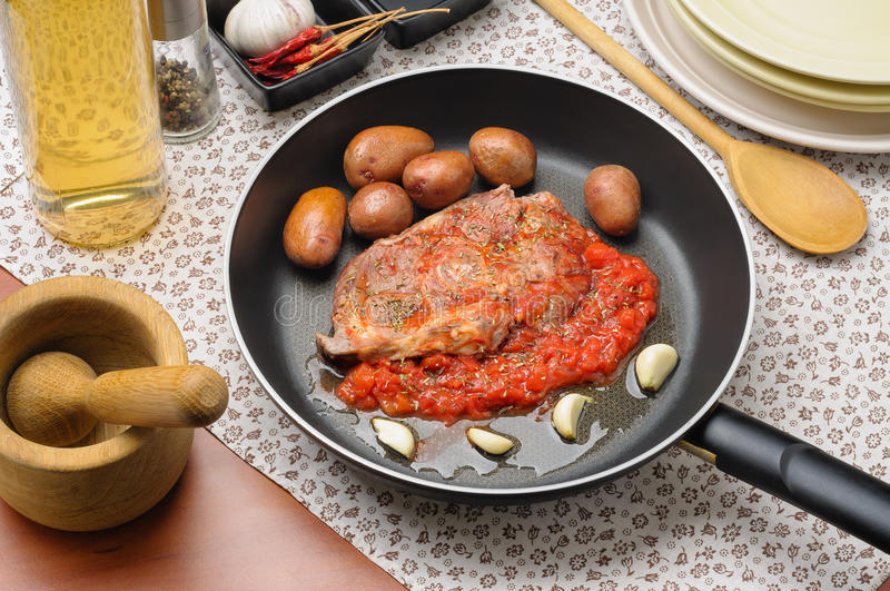 Sliced Mutton Leg in Provencal Way. Preparation of ossobuco with tomato, garlic and provencal aromatic herbs, with small new potatoes stock photo