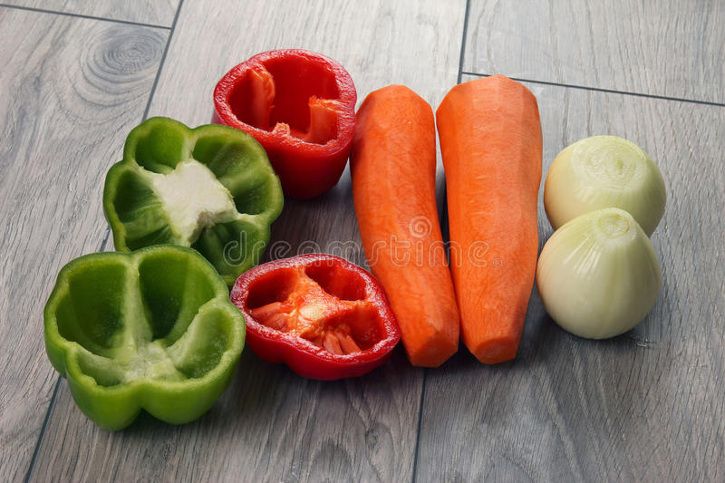 Sliced onion and pepper on a kitchen board with and carrots. The sliced onion and pepper on a kitchen board with and carrots stock images