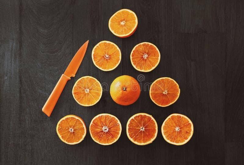 Sliced Orange Fruit With Knife stock photography