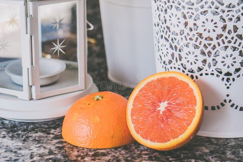 Sliced of Orange Fruit Near on White Framed Glass Candle Lantern royalty free stock images