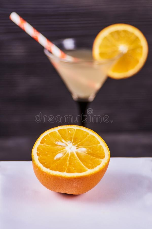 Fresh orange martini. Sliced orange next to martini goblet with fresh orange juice and orange slice, cocktail tube, on a dark wooden background. Focus on orange royalty free stock images