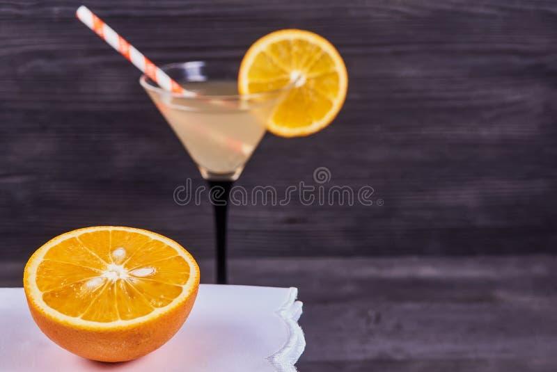 Fresh orange martini. Sliced orange next to martini goblet with fresh orange juice and orange slice, cocktail tube, on a dark wooden background. Focus on orange royalty free stock photography