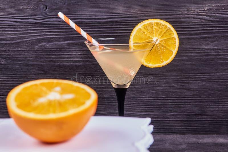 Fresh orange martini. Sliced orange next to martini goblet with fresh orange juice and orange slice, cocktail tube, on a dark wooden background. Focus on martini royalty free stock photo