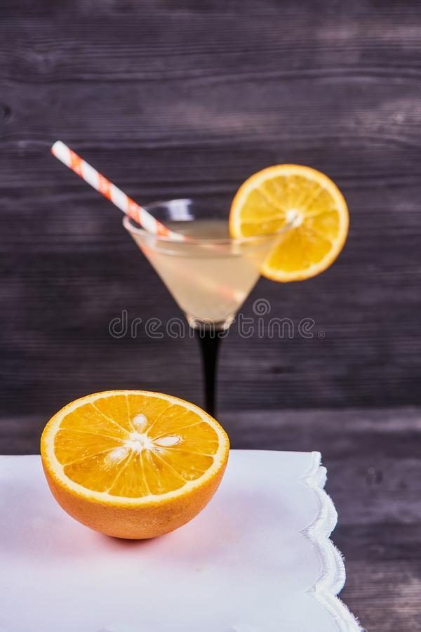 Fresh orange martini. Sliced orange next to martini goblet with fresh orange juice and orange slice, cocktail tube, on a dark wooden background. Focus on orange royalty free stock photos