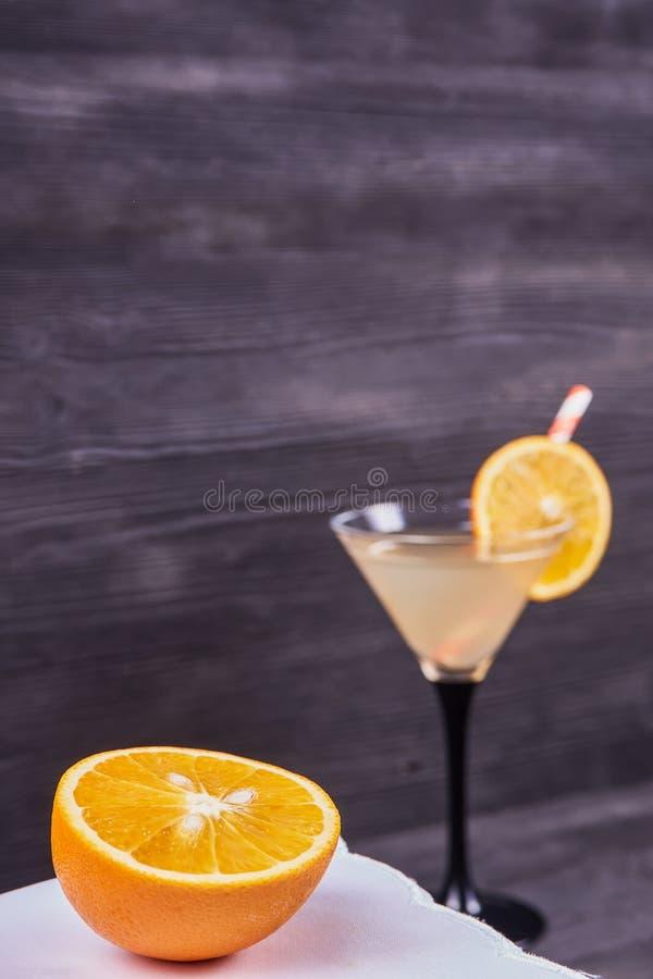 Fresh orange martini. Sliced orange next to martini goblet with fresh orange juice and orange slice, cocktail tube, on a dark wooden background. Focus on orange stock image
