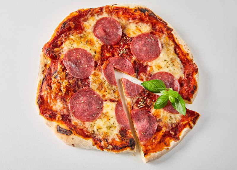 Sliced pepperoni pizza with fresh basil leaves stock images