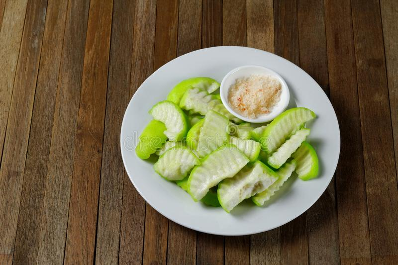 Sliced Pickled guava on white plate with salt and ground red or green peppers, eaten as a condiment stock photo