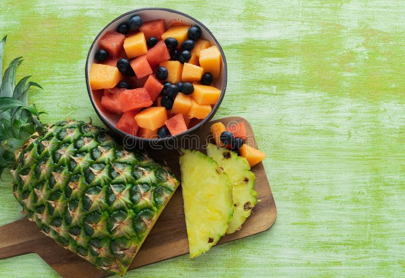 Sliced pineapple and bowl of fruits on green wooden background royalty free stock images