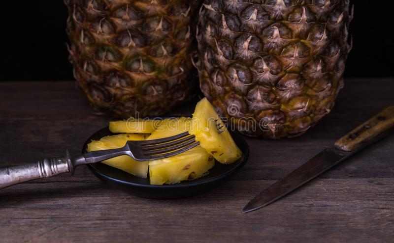Sliced pineapple on old rustic desk with knife and with whole pineapple behind. Black background stock photo