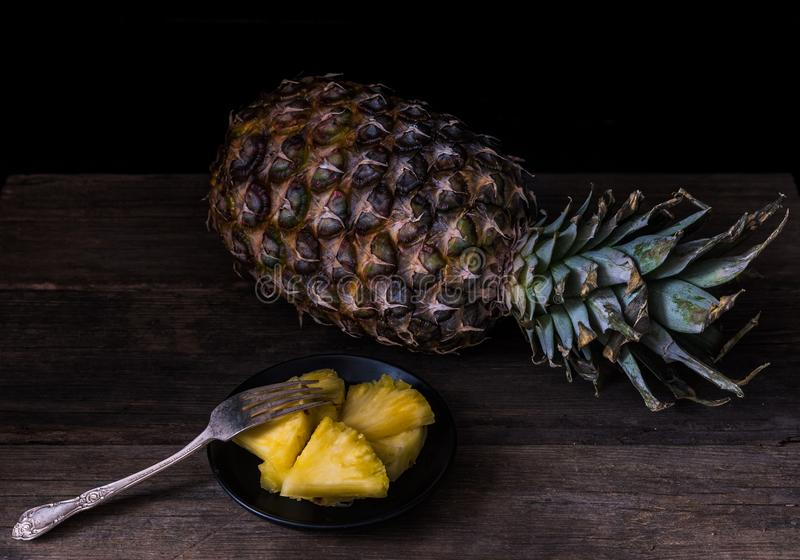 Sliced pineapple on old rustic desk with knife and with whole pineapple behind. Black background.  stock photo