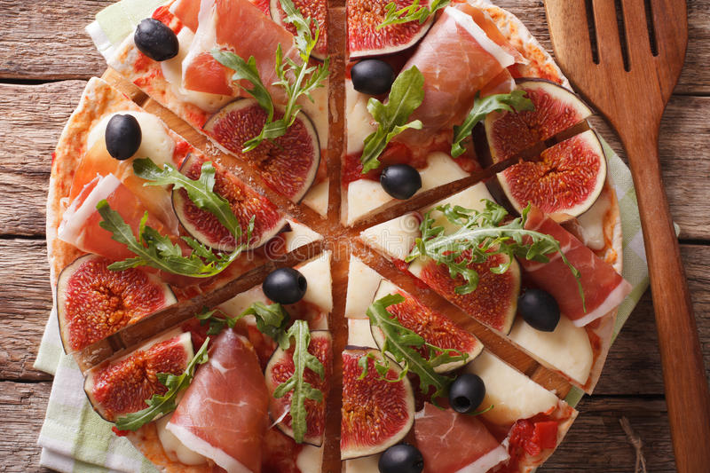 Sliced pizza with figs, ham, cheese and arugula close-up. Horizo royalty free stock image