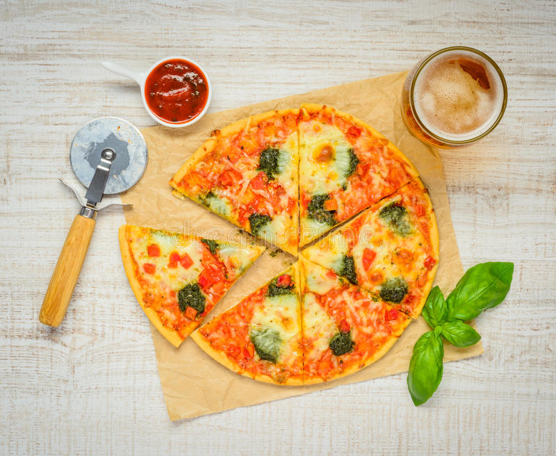 Sliced Pizza with Tomato Sauce and Glass Beer royalty free stock photo