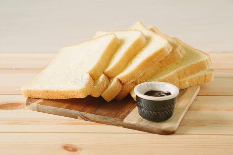Sliced plain bread and jam on wooden tray stock image