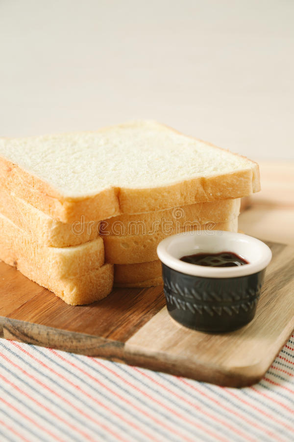 Sliced plain bread and jam on wooden tray stock images