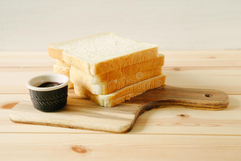 Sliced plain bread and jam on wooden tray stock photo