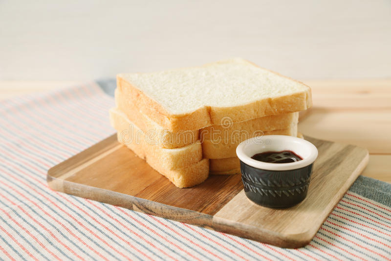 Sliced plain bread and jam on wooden tray royalty free stock images