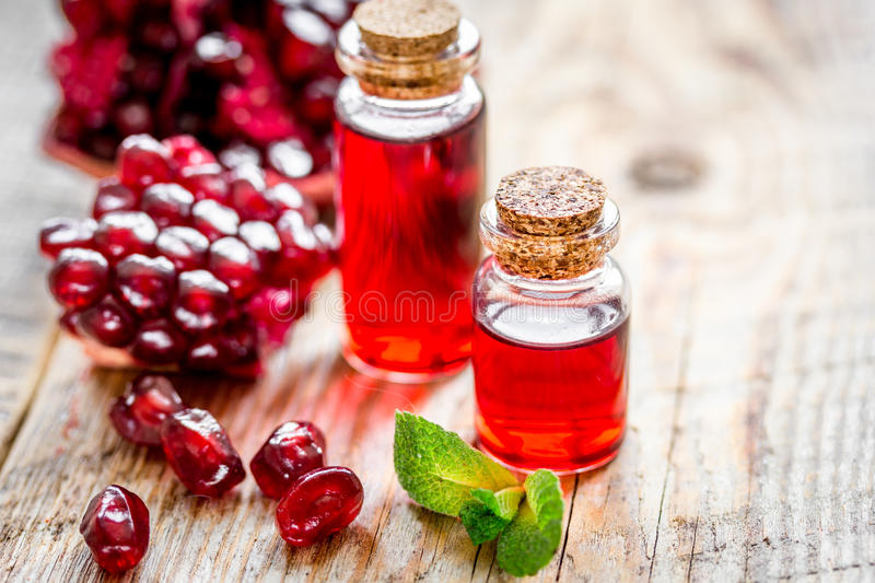 Sliced pomegranate and extract in glass on wooden background royalty free stock photos