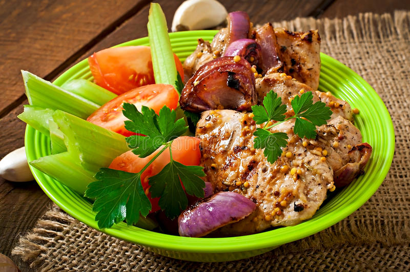 Sliced pork grilled with vegetables. On plate stock photos