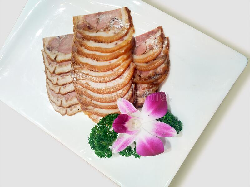 Sliced pork marinated products, square white porcelain dishes and Chinese dishes decorated with flowers. Cooking dishes photography. Sliced pork marinated stock photography