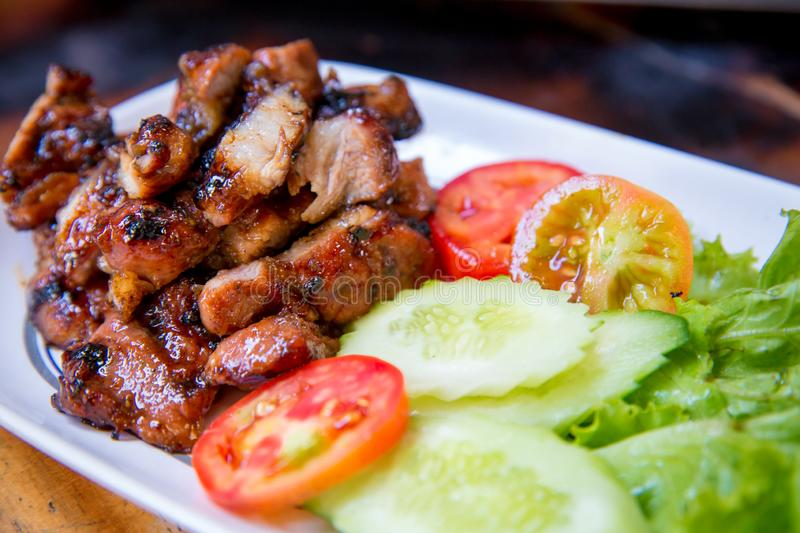 Sliced pork roasted thai style with green leaves salad on rustic plate with cutlery. Charcoalboiled pork neck Grill pork Thai style food royalty free stock image