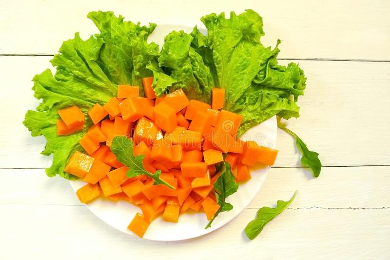 Sliced pumpkin slices on lettuce leaves with pine nuts and arugula. Olive oil, honey and Provencal herbs. Supply of salad in a stock images