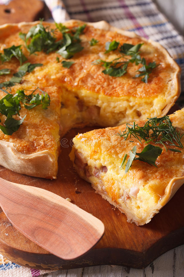 Sliced quiche with cheese, eggs and bacon close-up on a board. v stock photography