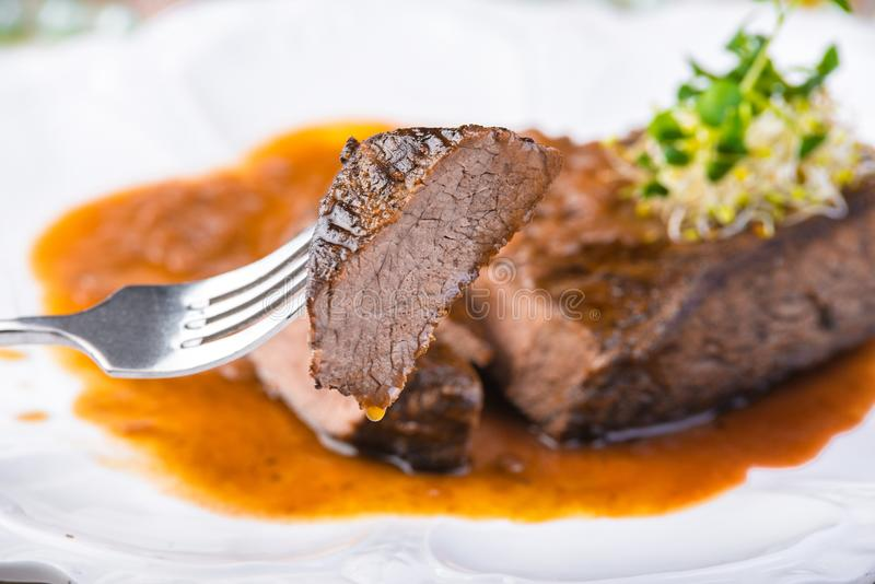 Sliced rare grilled Beef steak Ribeye with sauce on white plate. Selective focus royalty free stock image