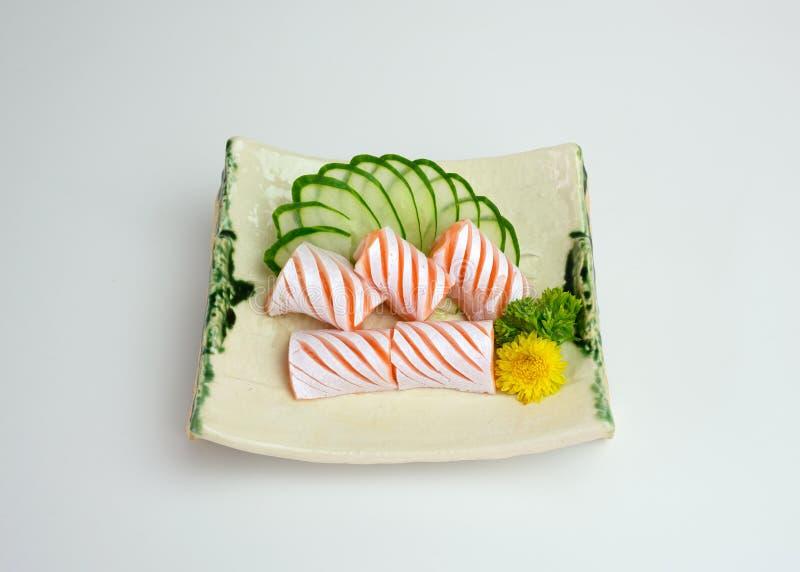 Sliced raw Salmon sac sashimi with cucumber on plate. Sliced raw Salmon sac sashimi with cucumber on ceramic plate royalty free stock photography