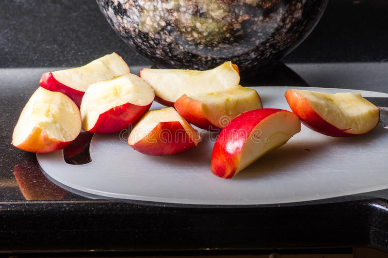 Sliced red apples on cutting board with bowl royalty free stock image