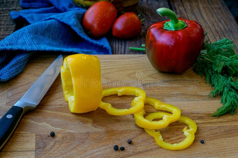 Sliced bell peppers on wooden background. Sliced red and yellow bell peppers on a wooden cutting board with a kitchen knife and scattered pepper and a bunch of stock image