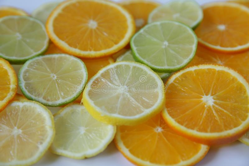 Sliced rings of orange and lemon, and lime isolated on white background stock photos