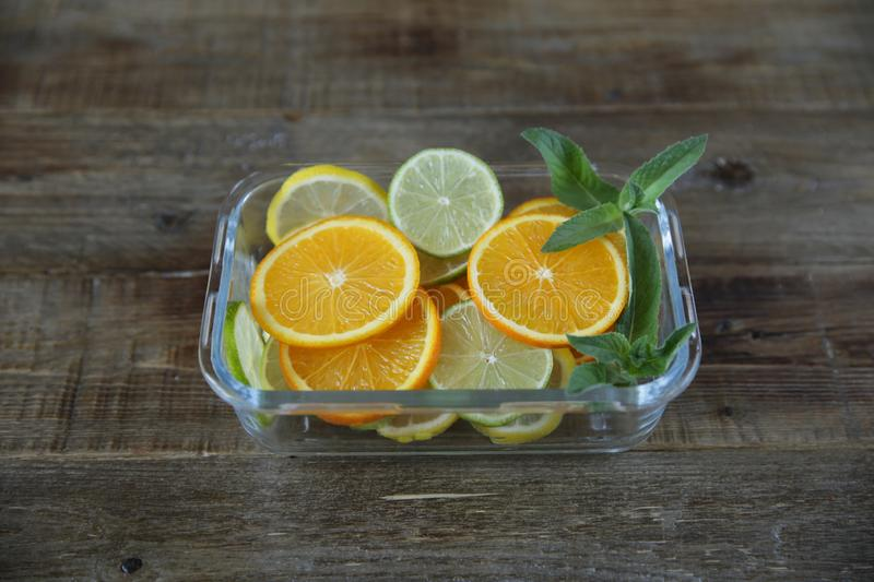 Sliced rings of orange, lemon, lime and sprig of mint in a glass plate on a wooden rustic background. Healthy food. stock image