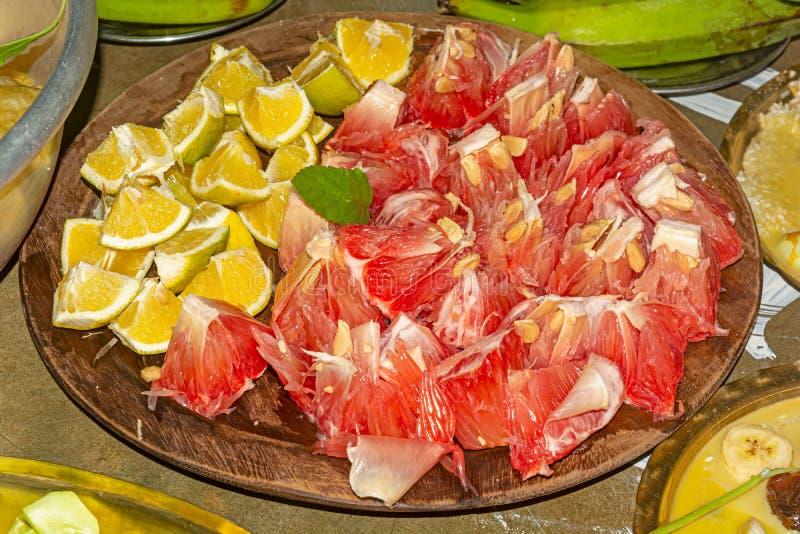 Sliced ripe Pomelo and Kabosu lemon fruit on a wooden plate. Served to Laxmi goddess as prasad.close up royalty free stock image