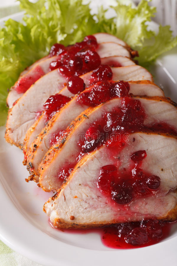 Sliced roasted turkey breast with cranberry sauce close-up. vert. Sliced roasted turkey breast with cranberry sauce on a plate close-up. vertical royalty free stock images