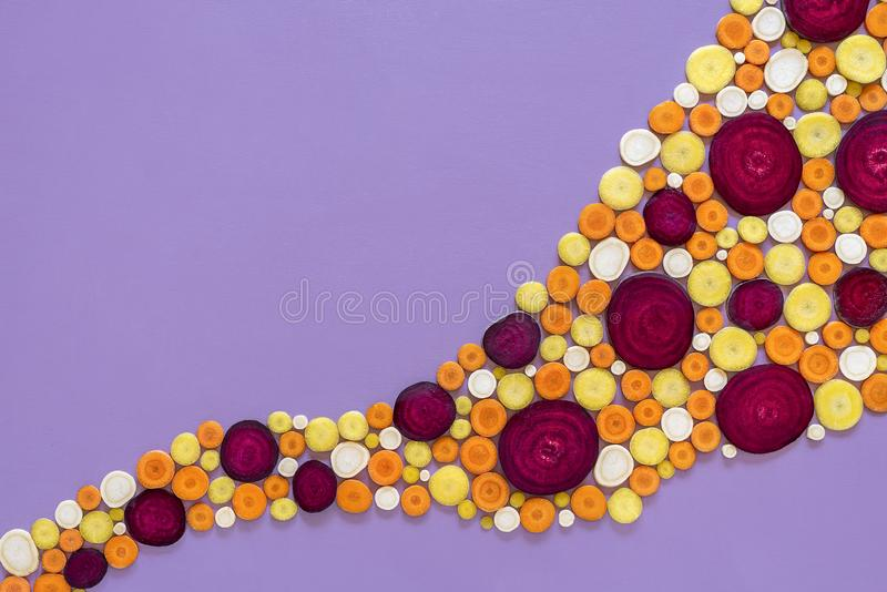 Sliced root vegetables background. Winter vegetables. Slices of vegetable roots isolated on a purple background. Above view of cold season vegetables. Winter stock images