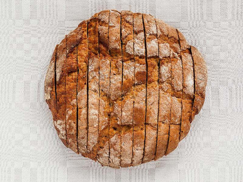 Sliced round loaf of rye bread with an appetizing crispy brown crust on a gray linen tablecloth. Tasty, usefull and nutritious. stock image