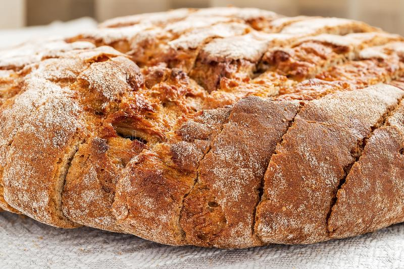 Sliced round loaf of rye bread with an appetizing crispy brown crust on a gray linen tablecloth. Tasty, usefull and nutritious. stock photography