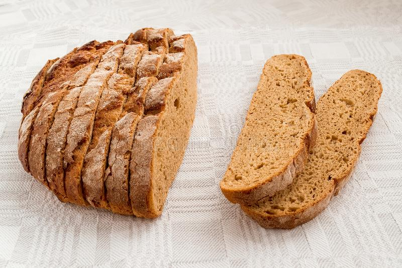 Sliced round loaf of rye bread with an appetizing crispy brown crust on a gray linen tablecloth. Tasty, usefull and nutritious. stock photo