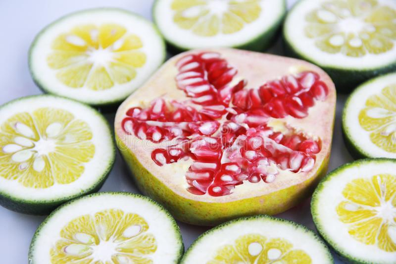 Sliced round slices of red natural pomegranate with grains and slices of yellow lime lemon stock images